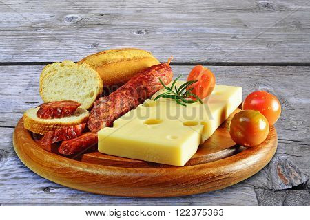 Emmental cheese and chorizo pork sausage on chopping board over wooden table.