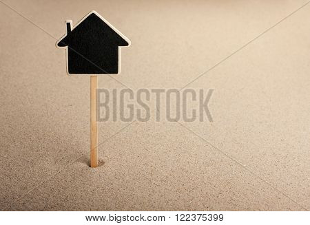 Pointer ads board in the form house in the sand can be used as background