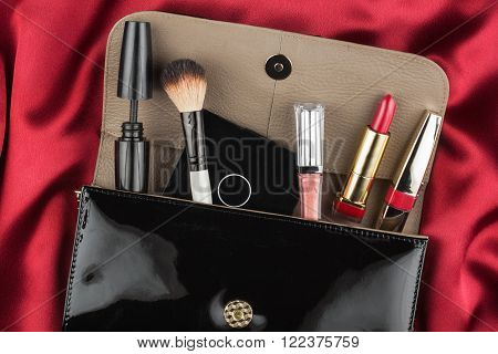 Fashion concept. Black patent leather bag with cosmetics on red background