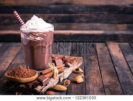 Chocolate milkshake with whipped cream on the wooden rustic table