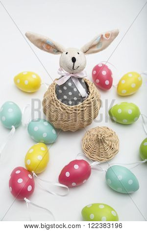 Toy Easter bunny with long ears, with a bow in a gray polka-dot dress in a wicker basket with a lid with colorful dyed eggs on white background