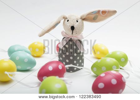 Toy Easter bunny with long dropping ear , with a bow in a gray polka-dot dress with colorful dyed eggs on white background