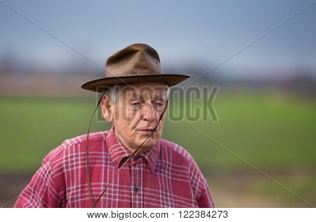 Portrait of old farmer with hat and plaid shirt walking on the field