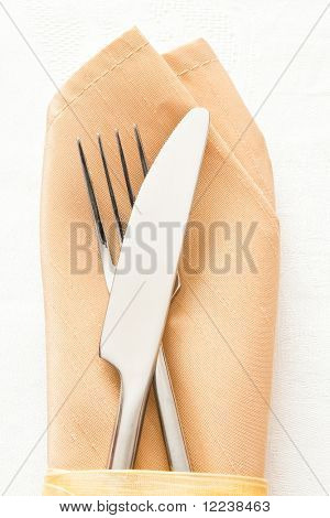 knife and fork on beige napkin