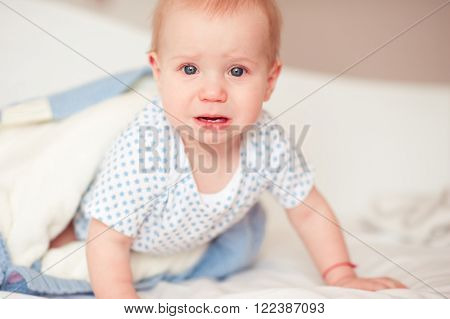 Crying baby boy crawling in bed in room. Looking at camera. Childhood. Sadness.