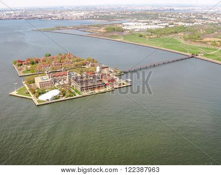 Spectacular helicopter view of Ellis Island, an islet at the mouth of Hudson River in New York Harbor, visited using the same ticket and ferry that allows access to the nearby Statue of Liberty.