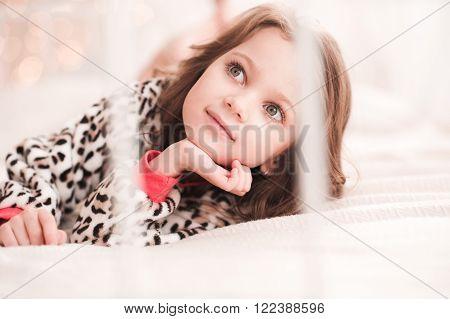 Cute baby girl 4-5 year old wearing pajama closeup. Posing over lights. Bedtime. Childhood.