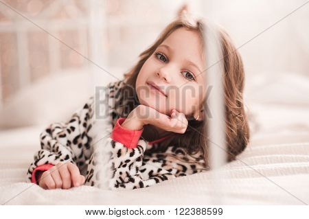 Cute kid girl 4-5 year old wearing pajama in bed closeup. Posing over lights at background. Looking at camera. Bedtime. Childhood.
