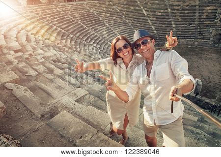 Positive young couple take selfie photo in Side antique amphitheater