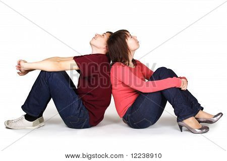 Young Man And Woman Sitting Back To Back And Looking Up, Isolated