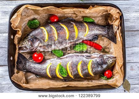 delicious raw trout fishes prepared for baking with potatoes broccoli lemon tomatoes and spices in baking dish on a wooden background top view horizontal