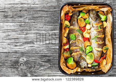 whole trout fishes grilled with potatoes broccoli lemon tomatoes top view