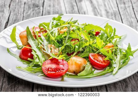 Fresh low-calories salad with chicken breast arugula and tomatoes closeup