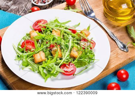 low-calories salad with chicken breast arugula and tomatoes close-up