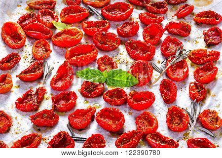 Sun dried tomatoes on a white baking paper with basil