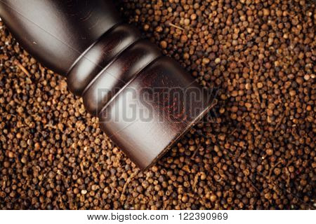 pepper mill on peppercorns background
