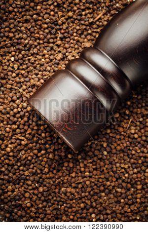 pepper mill on peppercorns background