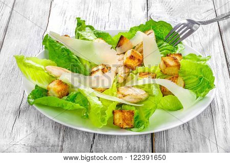 Caesar salad with cos lettuce croutons and grilled chicken breast on the white dish on an old wooden table close-up