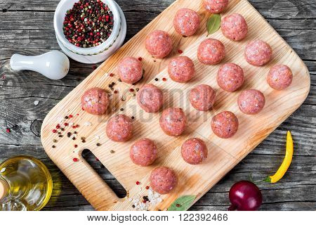 raw meatball on a cutting board prepared for cooking
