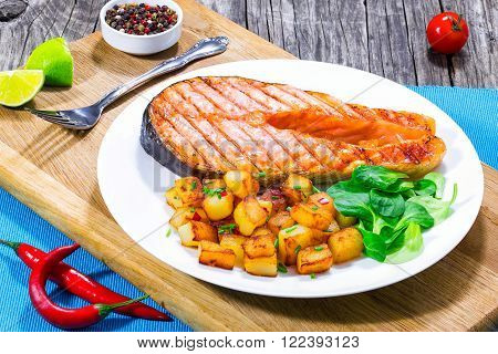 grilled salmon steak with fried potatoes top view