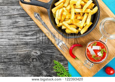 Potato Fries with pieces of chili pepper on the white dish and Slices of marinated Norwegian herring in tomato sauce on the pieces of rye bread the glass jar with delicious herring with dill top view