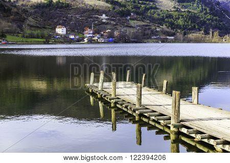 Wooden pier on the Cubuk lake and village background mountainside. Cubuk lake near Goynuk province in Bolu Turkey.