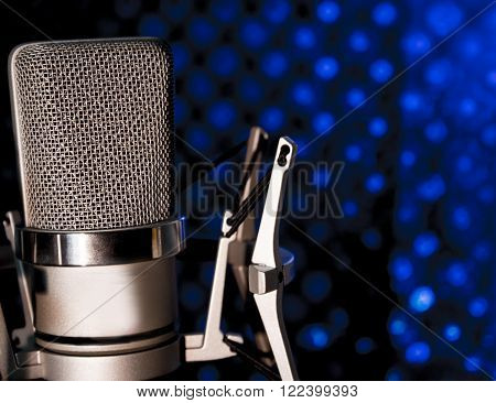 Silver microphone on black and blue background