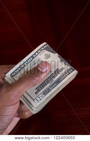 Hand full of money holding 20 Dollar Bill