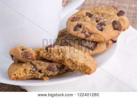 Chocolate chip cookies on a plate with a coffee cup