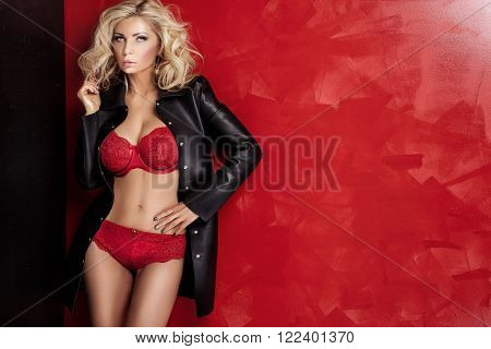 Blonde sexy lady with glamour makeup and long curly hair posing in studio. Elegant woman wearing sensual lingerie.