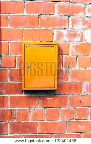 Stone and metal. Red orange brick wall orange mailbox. The texture of the surface of a brick wall with a box for letters from the street.