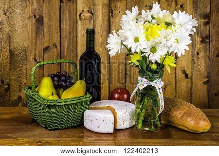 picnic basket of fruits cheese bread wine and flower bouquet