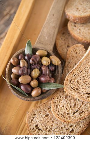 Aperitif made of bread with mixed olives in brine of Tuscany Ital