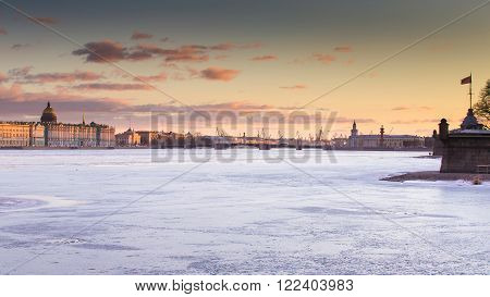 Russia Saint-Petersburg 19 March 2016: The water area of the Neva River at sunset the Winter Palace Palace Bridge the dome of St. Isaac's Cathedral pink clouds frozen river