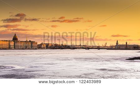 Russia, Saint-Petersburg, 19 March 2016: The water area of the Neva River at sunset, the Winter Palace, Palace Bridge, the dome of St. Isaac's Cathedral, pink clouds, frozen river