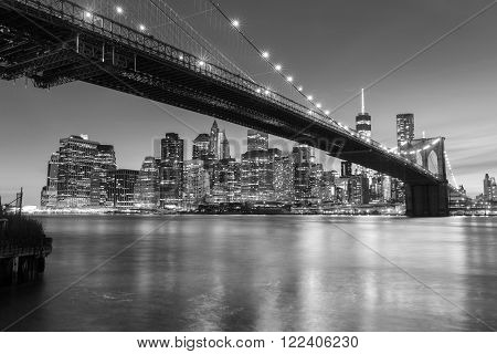 Brooklyn Bridge at dusk viewed from the Brooklyn Bridge Park in New York City. Black & White photo.