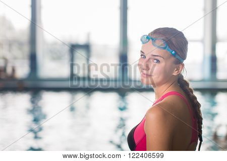 Female swimmer in an indoor swimming pool - looking at the camera, smiling wholeheartedly (shallow DOF; color toned image)