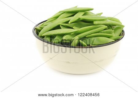 sugar snaps in an enamel bowl on a white background