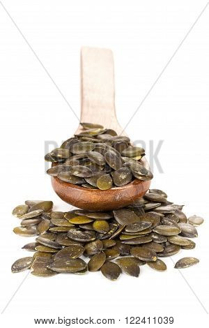 Unshelled pumpkin seeds in wooden spoon over white background