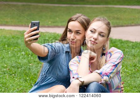 two young women friends doing selfie phone. summer nature