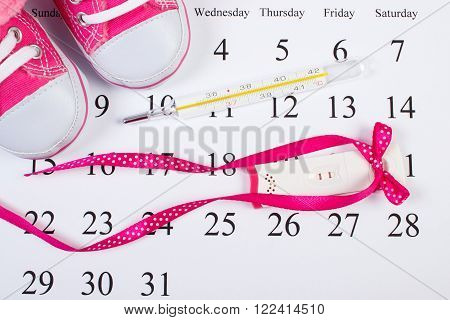 Pregnancy test with positive result, thermometer for measuring and baby shoes on calendar, concept of extending family and expecting for baby