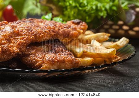 Fried fish in crispy batter with chips on a plate