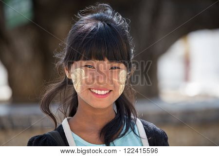 MANDALAY MYANMAR - JANUARY 16 2016: Unidentified young Myanmar girl with thanaka on her smile face is happiness. Thanaka is a yellowish-white cosmetic paste made from ground bark.