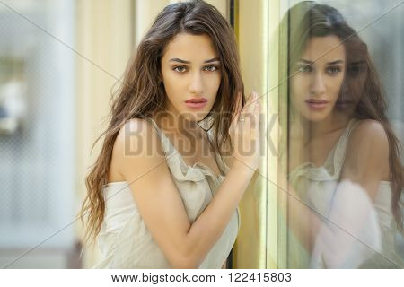 Portrait close up of young beautiful brunette woman in beige dress, Specular reflection in a shop window