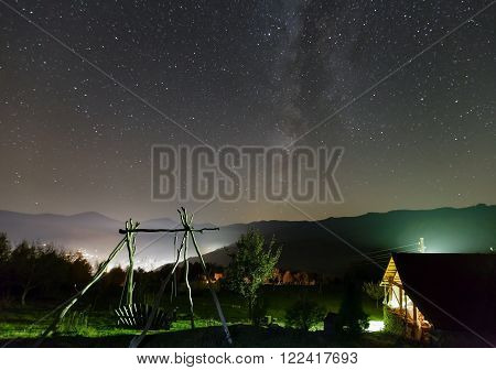 Milky Way in starry night sky and rural yard illuminated in green color on mountain hill.