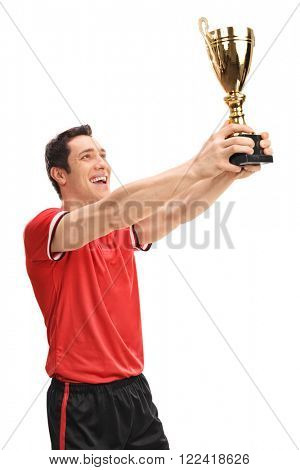Vertical shot of a joyful young football player lifting a trophy isolated on white background