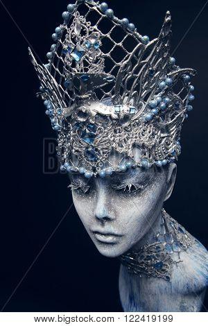 Mannequin in creative silver snow queen crown  on black background