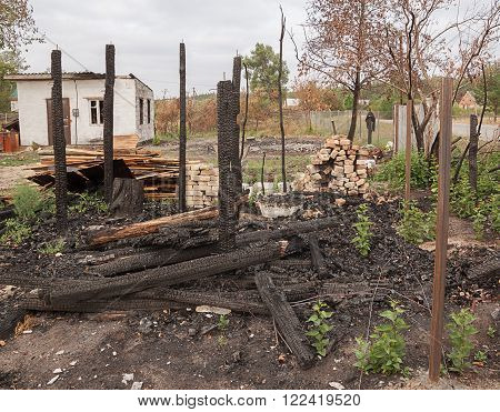 The charred ruins and remains of a burned down house near the road