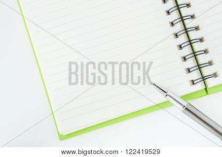 Open notebook with metallic ball pen. Selective focus.