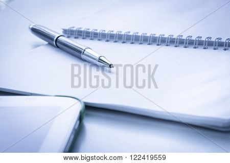 Open Notebook With Metallic Ball Pen And Tablet